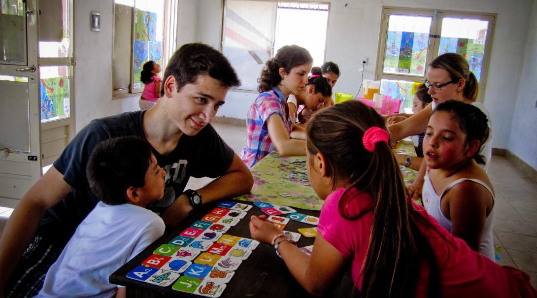 Adolescente en su voluntariado social ayuda a niños pequeños en una primaria.
